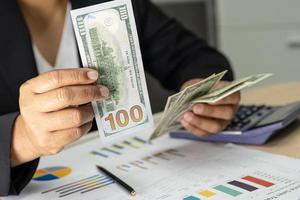 Contador asiático sosteniendo billetes de dólares estadounidenses con gráfico. foto