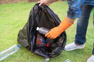 voluntario mujer asiática llevar botellas de plástico de agua en la bolsa de basura foto