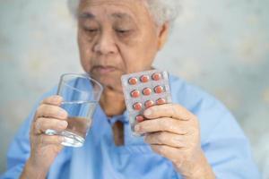 Asian senior woman patient holding antibiotics capsule pills photo