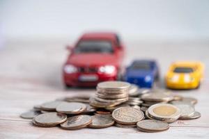 coche sobre fondo de monedas, préstamo de coche, finanzas foto