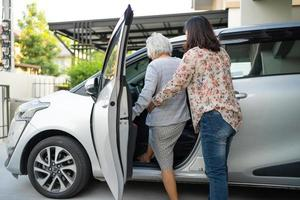 Help and support asian senior  woman patient prepare get to her car. photo