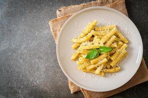 Pesto Rigatoni pasta with parmesan cheese - Italian food and vegetarian food style photo