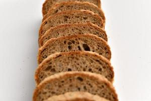 Slices of rye bread on white background photo