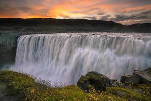 Detifoss waterfall with sunset in the background photo