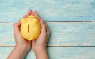 Hand hold piggy bank for save money on wooden background photo