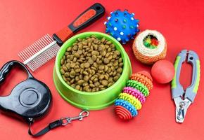 Pet food in bowls, toy, for pets on red background photo