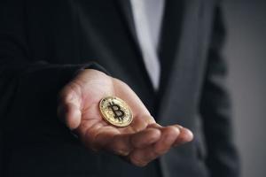 Empresario de traje negro sosteniendo un bitcoin dorado sobre fondo oscuro foto