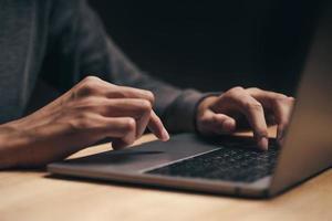 hombre usando una computadora portátil en la mesa de madera, internet, buscar, navegar foto