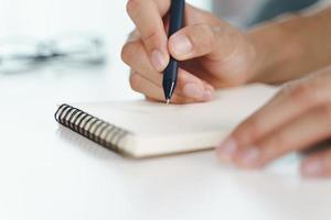 Las manos del hombre usan la pluma escribiendo en el bloc de notas sobre la mesa foto