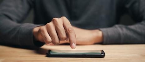 Man using smartphone on wooden table, searching, browsing, message photo