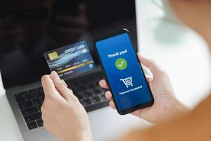Mujer sosteniendo una tarjeta de crédito y usando un teléfono inteligente para compras en línea foto