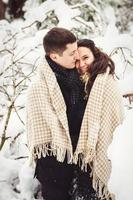 Guy and a girl in clothes and scarves on a walk in the snowy weather photo
