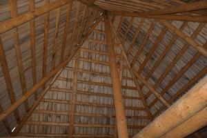Beams made of logs under the dome of the roof photo
