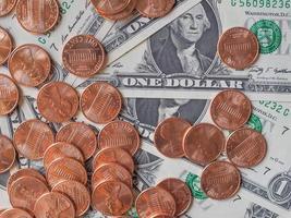 monedas y billetes de dólar foto