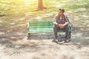 Young hipster man  sitting on a wooden bench in the park. photo