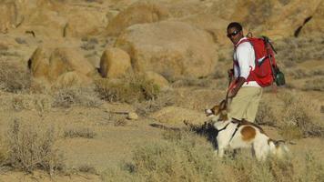 een jonge man backpacken in een bergachtige woestijn met zijn hond. video