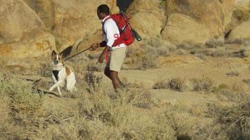 un jeune homme faisant de la randonnée dans un désert montagneux avec son chien. video