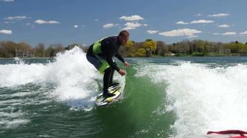 un uomo wake surf wakeboard dietro una barca su un lago. video