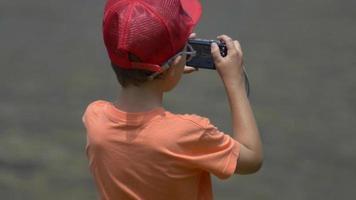 un garçon près d'un lac de montagne en train de prendre des photos. video