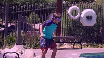 een jongen springt en doet een kanonskogel in een zwembad in een hotelresort. video