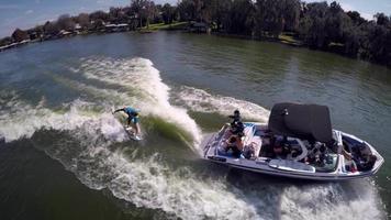 ripresa aerea di un uomo wakeboard wake surf dietro una barca su un lago. video