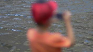 un niño cerca de un lago de montaña tomando fotografías. video