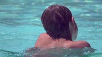 un garçon joue dans une piscine dans un complexe hôtelier. video