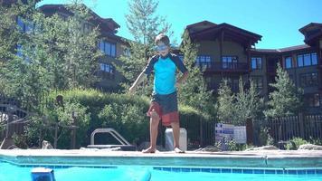 een jongen speelt en springt in een zwembad in een hotelresort. video