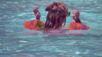 une fille joue dans une piscine dans un complexe hôtelier. video