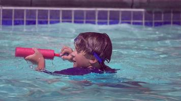 A boy plays in a pool at a hotel resort. video