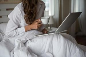 Happy Beautiful woman working on a laptop on the bed in the house photo