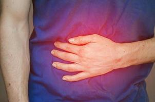 A man holding his stomach. Close up. photo