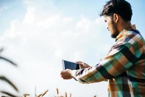 Granjero inteligente comprobando la granja de cebada con tablet PC foto