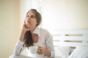 Bella mujer en su dormitorio tomando café por la mañana foto