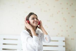 Beautiful woman listening music in morning sitting on bed at home photo