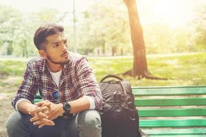 Young hipster man with backpack beside sitting on a wooden bench. photo