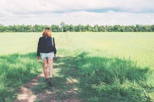 parte posterior de la mujer joven que lleva la cámara retro en el campo de hierba disfrutar foto