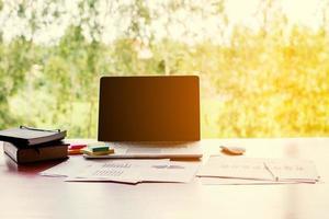 lugar de trabajo de oficina de concepto de negocio con ordenador portátil en la mesa de madera. foto