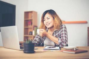 Young business woman sitting in office desk with cup of coffee ready. photo