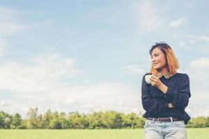Back of happy young woman standing on green field enjoy with fresh air photo
