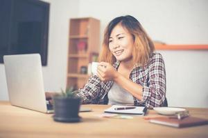 Young business woman sitting in office desk with cup of coffee ready photo