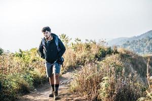 Hombre que viaja con mochila de senderismo en las montañas foto