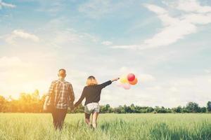 parte posterior de la feliz pareja asiática joven sosteniendo globo y caminar juntos. foto