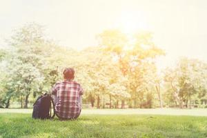 Vista trasera del relajado joven viajero sentado sobre la hierba en el parque. foto