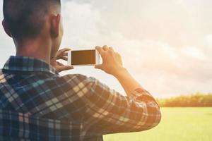 hombre joven inconformista con smartphone tomando la fotografía de paisaje. foto