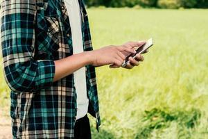 Primer plano de manos de hombre hipster usando su teléfono inteligente al aire libre en el parque foto