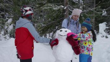 mãe e filhos construindo um boneco de neve juntos video