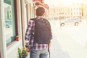 Rear of young traveler with backpack on an adventure vacation photo