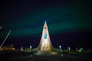 auroras boreales brillando sobre la iglesia en reykjavik foto