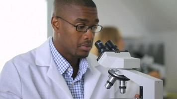 Man looking into microscope video